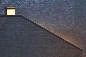 """<div class=""""10.6 Bildunterschrift"""">Für die Fassade wurde der Ziegel Pescara FKSG des Ziegelherstellers GIMA verwendet. Der schwarz durchgefärbte Ziegel ist traditionell mit Kohle-Salzbrand-Technologie gefertigt und bezieht sich auf die regionale Backsteintradition</div>"""