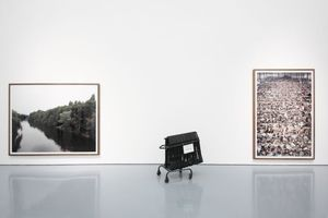 """Ausstellungsansicht. Rechts: """" Nha Trang"""", Gursky 2004, links ein Flussbild, dazwischen ein Stuhlständer für Besucher mit müden Füßen oder der nötigen Zeit, die man vor manchem Bilder verbringen sollte"""