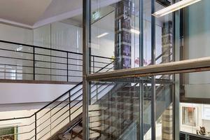 """<div class=""""10.6 Bildunterschrift"""">Die freigelegten Zeitzeugen, wie das Treppengeländer, harmonieren mit der zurückhaltenden Gestaltung der weißen Wände und Decken. Lediglich die Keramik verkleideten Stützen heben sich farblich ab</div>"""