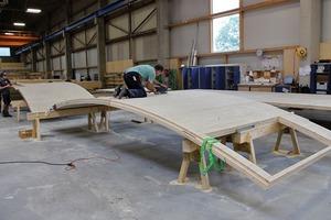 Die gebogenen Brettsperrholzplatten wurden durch einen speziellen Formenbau und Vakuumtechnologie hergestellt. Neben den gebogenen Wandbauteilen wurden die runden Plattenränder der ebenen Deckenbauteile mittels CNC Technik angepasst. Der Produktionsprozess von flachen und gebogenen Brettsperrholzplatten unterscheidet sich durch den zusätzlich notwendigen Formbau und dem Pressen der Platten in ihre Form. Der Abbund erfolgte auf einem 8-Achsen Roboter. Pro Tag wurden so ein bis zwei Bauteile gefertigt