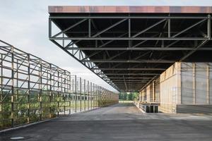 Neoprenkissen entkoppeln den Durchlaufträger in der Fassadenebene und übertragen dennoch die statische Last.<br />Die Vegetationswand links schafft den Übergang zur Natur<br />