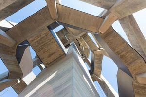 Die innen-/außenliegende Treppe umschlingt den Liftschacht