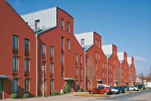 Die Häuser des ersten Bauabschnitts sehen noch sehr gut aus. Kein Graffiti oder andere Spuren von Vandalismus sind hier zu finden. Der respektvolle Umgang, den Architekt und Bauherr gegenüber den zukünftigen Bewohnern gezeigt haben, zahlt sich offensichtlich aus. Die Rottöne der letzten beiden Bauabschnitte unterscheiden sich von den ersten, da sich die Farbe durch das UV-Licht in den nächsten Jahren noch angleichen soll. Falls nicht, tut dies dem Gesamtkonzept keinen Abbruch. Im Gegenteil – auch das ist Urbanität