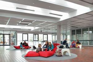 Die Flurzonen und die Aula werden über mehrere Flachdachfenster mit Tageslicht versorgt und in lichtdurchflutete Spiel- und Lernzonen verwandelt