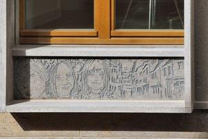 Die Gesichter der Bauherrenfamilie sind auf der Fassade verewigt – geritzt in steinernen Brüstungen