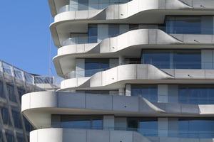 Die zurückgesetzten Fassaden werden durch die überhängenden geschwungenen Terrassen auf natürliche Weise verschattet. So konnte auf einen konventionellen außen liegenden Sonnenschutz verzichtet werden<br />