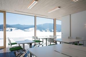 """<div class=""""9.6 Bildunterschrift"""">Die Elemente der Ligno AkustikDecke aus profilierten Weisstanne-Paneelen fügt sich in das minimalistische Gestaltungskonzept mit der regionaltypischen Holzart für Fassade und Fenster sowie der Farbe Weiß für die Innenraumgestaltung ein. Ein dunkler Eiche-Parkettboden bietet den notwendigen Kontrast</div>"""