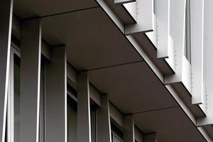 Die aufgesägten Aluminiumprofile wurden so aneinandergesetzt, dass sie wellenförmig von oben nach unten an der Fassade herunter zu laufen scheinen