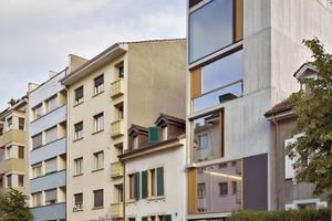 Bedingt durch die geringe Parzellenbreite und die beschränkte Gebäudetiefe musste in die Vertikale entwickelt werden. Die Lösung hierfür war die Stapelung von zwei Triplex-Häusern