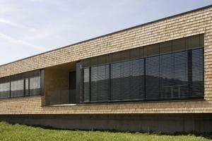Die Elemente der Ligno Akustik-Decke aus profilierten Weisstanne-Paneelen fügt sich in das minimalistische Gestaltungskonzept mit der regionaltypischen Holzart für Fassade und Fenster sowie der Farbe Weiß für die Innenraumgestaltung ein. Ein dunkler Eiche-Parkettboden bietet den notwendigen Kontrast.