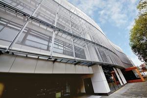 Die sich über die gesamte Gebäudelänge erstreckende Gewebefassade aus Edelstahl besteht optisch aus drei horizontal verlaufenden Gewebebändern. Die transparente Fassadenverkleidung ermöglicht die unverstellte Sicht aus den lichtdurchfluteten Klasseräumen nach außen<br />