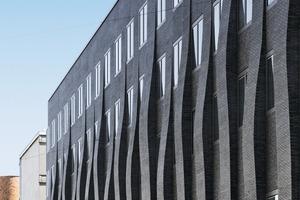 Für die Fassadensanierung wurde ein spezieller titangrauer Klinker in dem Sonderformat 140x115x40 mm produziert. Auch die mattglänzende Glasur ist eigens dafür entwickelt worden. Aufgrund ihrer Ähnlichkeit zu einer keramischen Salzbeschichtung wird das auf die Fassade geworfene Licht gebrochen<br />