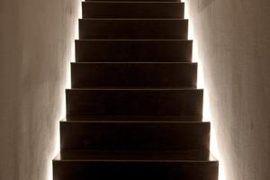 """<div class=""""4.1 Bildunterschrift"""">LED-Licht lässt die  Treppe zum Keller und Büro scheinbar schweben. Das App für das Smart-Phone, mit dem man das BUS-System ansteuern kann, ist noch Zukunftsmusik</div>"""