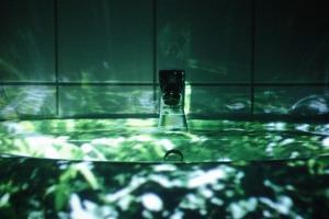 """""""Die Kleine Welt"""" konzentriert sich auf ein Waschbecken, das den ganzen Raum in eine ruhige, kontemplative Stimmung hüllt. Die Projektion wird vom Wasser im Becken in den ganzen Raum reflektiert. Durch die gefliesten Wände hallt das stetige Tropfen des Wasserhahns<br />"""