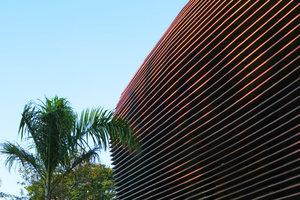 """<div class=""""10.6 Bildunterschrift"""">Die Gebäudehülle wird  Teil des  Außenraums: die Holzlamellen des Sonnenschutzes bilden Treppenstufen und Sitzmöglichkeiten</div>"""