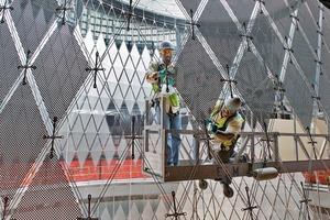 952 perforierte hochreflektierende Aluminiumpaneele hängen an dem gespannten Stahlnetz, das die Kontur der Kuppel nachzeichnet
