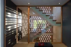 """Durch das """"Häkelmuster"""" entsteht ein Lichtspiel im Treppenraum des Hauses, das bis in die Wohnräume leuchtet. Eine Doppelstegplatte aus Plexiglas schließt die Lochfassade in den Innenraum ab"""