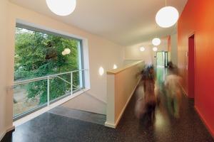 oben: Der Flur mit großem Garderobenbereichmitte: Eine orangefarbene Wand markiert den Haupteingang. Das Orange setzt sich im Inneren fort; entlang der Flure, der Wände und Türrahmen unten: Um die erhöhten Anforderungen an die Akustik zu erfüllen, erhielten die Klassenräume einen polygonaler Zuschnitt und spezielle Wandverkleidungen