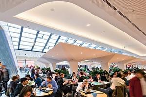 """<div class=""""9.6 Bildunterschrift"""">Oben: Dem Einkaufszentrum ist zur A5 ein Parkhaus vorgelagert, das den Verkehrslärm abschirmt und etwa 3000 Stellplätze aufnimmt </div><div class=""""9.6 Bildunterschrift"""">Unten: Die Esstische im Zentrum des Foodcourts überdachen skulpturale Schirme aus Gipskarton</div>"""