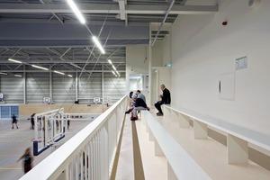 In die Sporthalle haben die Planer die Zuschauertribüne als Zwischengeschoss mit Lagerräumen unterhalb der Tribüne eingezogen