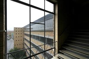 Blick auf dem Südlichen Treppentrum der Nordfassade auf den chromledergelben Hartbrand und die den Komplex umlaufenden Fensterbänder in Sichtbetonfassung
