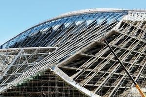 """<div class=""""9.6 Bildunterschrift"""">Eine Regelfläche aus Stahlgitter-</div><div class=""""9.6 Bildunterschrift"""">trägern als Fassade verbindet die zwei Ebenen von Tisch und Dach, welche eine selbsttragende Schalenstruktur erzeugt </div><div class=""""9.6 Bildunterschrift""""><strong>Dachfläche: </strong>28100 m²</div>"""