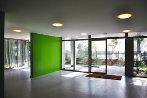 Die Bewohner kommen nun in einen großzügigen Eingangsbereich. Dank der Gestaltung mit Farben und den raumhohen Verglasungen wirkt er einladend