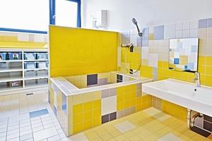 Im Innern des Kindergartens konzentriert sich die Farbgestaltung auf die zwei Bäder: Diese sind hell und bunt, das eine in Gelb- und das andere in Blaunuancen gehalten