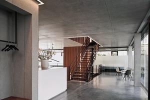 Die innere Gestaltung ist schlicht gehalten: sandgestrahlte Flächen aus Beton und Sichtbeton sowie Zement-Estrich als Bodenbelag. Über die Sichtbetondecke wird geheizt und gekühlt