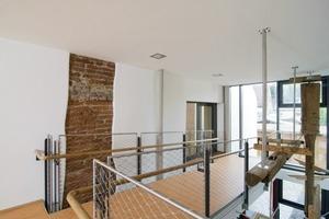 """<div class=""""13.6 Bildunterschrift"""">Passend zu den historischen Befunden und zur modernen Gestaltung mit Glas und Stahl wurden die Wände des Altbaus mit Reinkalkputz versehen</div>"""