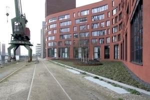 Der Verwaltungsbau schlängelt sich hinter einer ockerroten Putzfassade