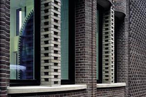 Der Schwung der Brüstungswölbung ist leicht asymmetrisch zu den hellen Lisenen ausgerichtet. Auch die Rahmenprofile der Fenster passen sich dieser Dynamik an und sind an der Seite der Pilaster breiter ausgeführt als auf der Seite der Lisenen