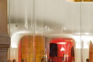 Der Glasvorhang wird von einem horizontalen Stahlband , von Edelstahlstangen in 6m Höhe in der Steindecke fixiert<br />