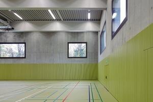 Der Hallenboden in Gelb-Grün und die korrespondierende Wandverkleidung ergänzen den vorherrschenden Beton farblich. Die Garderoben sind passend dazu in Bordeaux, die Nasszellen in Hellblau gehalten
