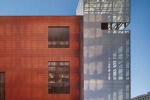 Der geschlossene Baukörper, bekleidet mit einer Sonderausführung der Alphaton-Ziegelfassade der Moeding Keramikfassaden GmbH, ruht teilweise auf einem zurückgesetzten, geschosshohen schwarzen Granitsockel. Grundsätzlich sind die 1100 mm x 417,5 mm großen Fassadenplatten kanneliert durch jeweils zwei, über die Plattenbreite verteilte angepresste Stege, die in bestimmten Bereichen als eigenständige Baguettes fortgeführt werden und so die Fassaden in luftige, lichtdurchlässige Gitterwerke auflösen.