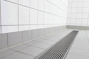 """<div class=""""9.6 Bildunterschrift"""">Durch die nivellierbaren Rinnenkörper und die Kombination mit 7x7mm Längsstabrosten fügen sich die Industrierinnen von Richard Brink bodengleich in die gefliesten Flächen ein. Da die Stegbreite der Roste 7mm beträgt, können sie barfuß bedenkenlos betreten werden</div>"""