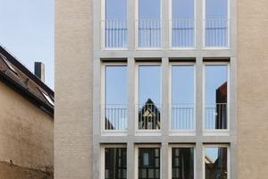 Die Fassade ist schlicht gehalten, Einfassungen aus Sichtbeton rahmen die Fenster<br />