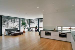 """<div class=""""9.6 Bildunterschrift"""">Die offene Wohnlandschaft wird von schmalen und breiten Fensterbändern belichtet. Im Sommer sorgt ein außenliegender Sonnenschutz für die Vermeidung von unerwünschten Wärmeeinträgen</div>"""