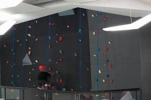 links: Eine Kletterwand zieht sich senkrecht durch alle Geschosse und schafft ein optisches und nutzbares Verbindungelement zwischen den Ebenen<br />