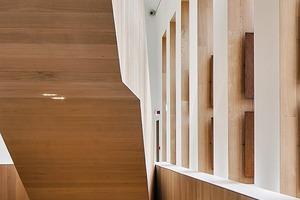 """<div class=""""13.6 Bildunterschrift"""">Die aus amerikanischer Weißeiche gebaute Treppe tritt skulptural in Erscheinung und leitet die Besucher auf die verschiedenen Ebenen. Die Holzarbeiten rund um Treppenhaus, Stufen und Treppenabsätzen wurden in 22mm starken Leisten ausgeführt. Um die Brandschutz-Bestimmungen zu erfüllen, wurde das Eichenholz mit einer feuerbeständigen Versiegelung vakuumimprägniert</div>"""