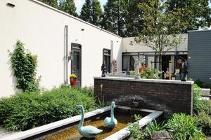 """<div class=""""10.6 Bildunterschrift"""">In den Vorgärten finden sich Gartenzwerge, im Brunnen Figuren von schwimmenden Schwänen – alles Details, damit sich die Bewohner wie zu Hause fühlen</div>"""