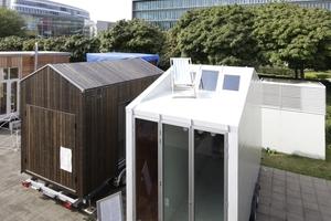 """Blick vom Gropius-Ensemble Bauhaus Archiv auf einige der dort temporär installierten Tiny Houses des bauhaus campus. Rechts der """"aVOID"""" von Leonardo di Chiara"""