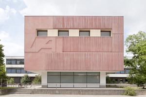 Aula IGS am Büssingweg / dRei Architekten BDA. Die Aula und Foyerbereiche wurden energetisch saniert und technisch in Stand gesetzt. Der Bauherr war, nach Darstellung der Kosten und Lebensdauerzyklen, von einer Lösung mit Betonfertigteilen überzeugt. Rot eingefärbter strukturierter Beton erinnert an einen in Falten liegenden Bühnenvorhang und verweist damit auf die Nutzung im Inneren