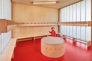 Die Architekten entwarfen auch das runde Möbel im Eingangsbereich: Laut Vorschrift muss es im Eingangsbereich eine Sitzgelegenheit für Erwachsene geben, während alle übrigen Möbel (Haken, Ablagen, Sitzbänke etc.) in kindgerechten Maßen zu gestalten sind