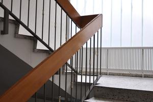 Bevor die Umbauarbeiten im gesamten Gebäude begannen, sah das Treppenhaus trostlos aus: endloser Handlauf und die immer wiederkehrende Fassade aus transluzentem Glas, die schummriges Licht in das Gebäude ließ