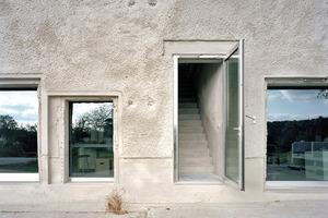 Während es sich bei den Bestandsaußenwänden nicht um Beton, sondern um Mauerwerk mit einem typischen geschlämmten DDR-Rauputz handelt, dominiert den minimalistisch gestalteten Innenraum neben Estrichboden, verputzten Innenwänden und der Verspachtelung der Dachunterseite der rohe Beton des Kerns