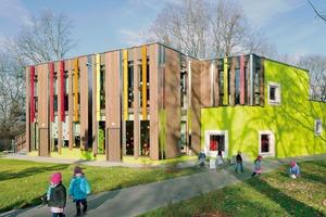 Das Gebäude ist in einen Massivbau und einen Holzskelettbau gegliedert. Diese Gliederung ist an den großen<br />und kleinen Fenstern erkennbar sowie an der unterschiedlichen Farbigkeit