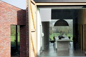 """<div class=""""16.6 Bildunterschrift"""">Die zwei großen Zufahrtstore zu beiden Seiten des Gebäudes wurden beibehalten und verglast. Dadurch entsteht ein großzügiger Durchblick vom neu entstandenen Innenhof bis zum schlossseitigen Garten</div>"""