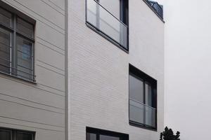 rechts oben: Der Neubau drängt sich durch seine dezente Farbgebung nicht in den Vordergrund. Lediglich die schwarzen Fensterrahmen fallen auf