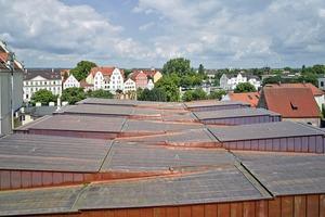 In der gefalteten Dachlandschaft finden sich die Zinnen und Türme der historischen Stadtmauer wieder. Das große Volumen der Baumasse fügt sich durch die bewegte Dachlandschaft harmonisch in die kleinteilige Parzellenstruktur der Altstadt ein